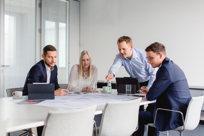 Besprechungssituation bestehen aus vier Mitarbeitern konzentriert auf einen Bauplan fotografiert in einem Besucherzimmer