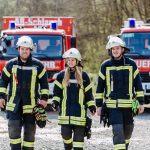 zwei Feuerwehrmänner und eine Feurwehrfrau auf dem weg zum Einsatz