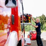 Ein Feuerwehrmann wie er das Equipment des Feuerwehrautos befüllt