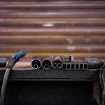 Industriefotografie Detailaufnahme von Metall auf dem Schweißtisch mit dem Schweißgerät