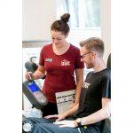 Personaltrainerin erklärt Kunden das Gerät im Fitnessstudio