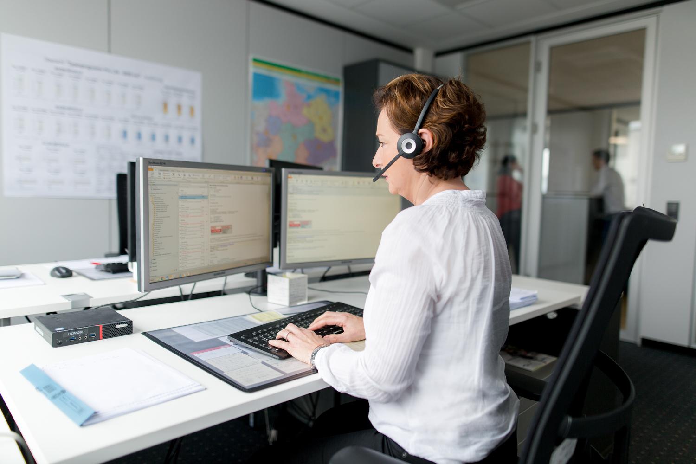 Frau in einer Schreibtischsituation mit einem Headset fotografiert