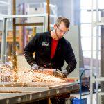 ein Mitarbeiter flext mit einer Flex an einem Metallrahmen von einem Container