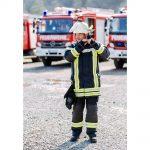Ein Feuerwehrmann im Portrait wie er sich einen Feuerwehrhelm anzieht