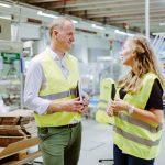 Zwei Personen stehen in einem Industriebetrieb und unterhalten sich