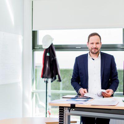 Unternehmensfotografie_Bauleiter in seinem Büro am Schreibtisch