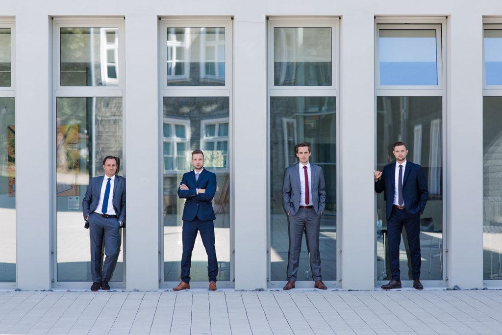 Vier Männer auf einem Foto mit Businesshintergund