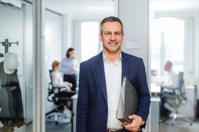 Fotografie in Unternehmen Mann mit Ordner vor einem Büro