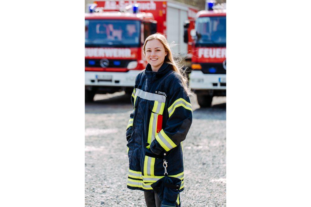 Feuerwehrfrau vor zwei Feuerwehrautos im Portrait