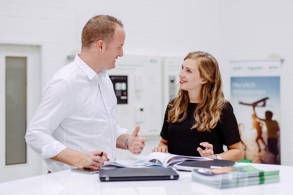 Zwei Mitarbeiter unterhalten sich in dem Eingangsbereich des Unternehmens fotografiert an einem Stehtisch
