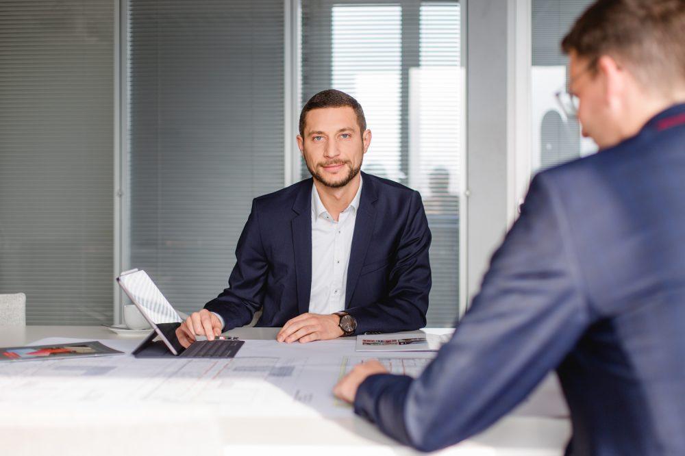 Mitarbeiterportrait an einem Besprechungstisch fotografiert in einer Gesprächssituation