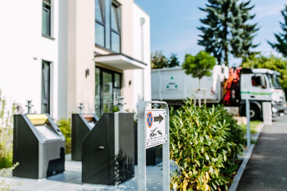 Detailaufnahme Unterflurbehälter der Abfallgesellschaft Mit Müllfahrzeug im Hintergrund