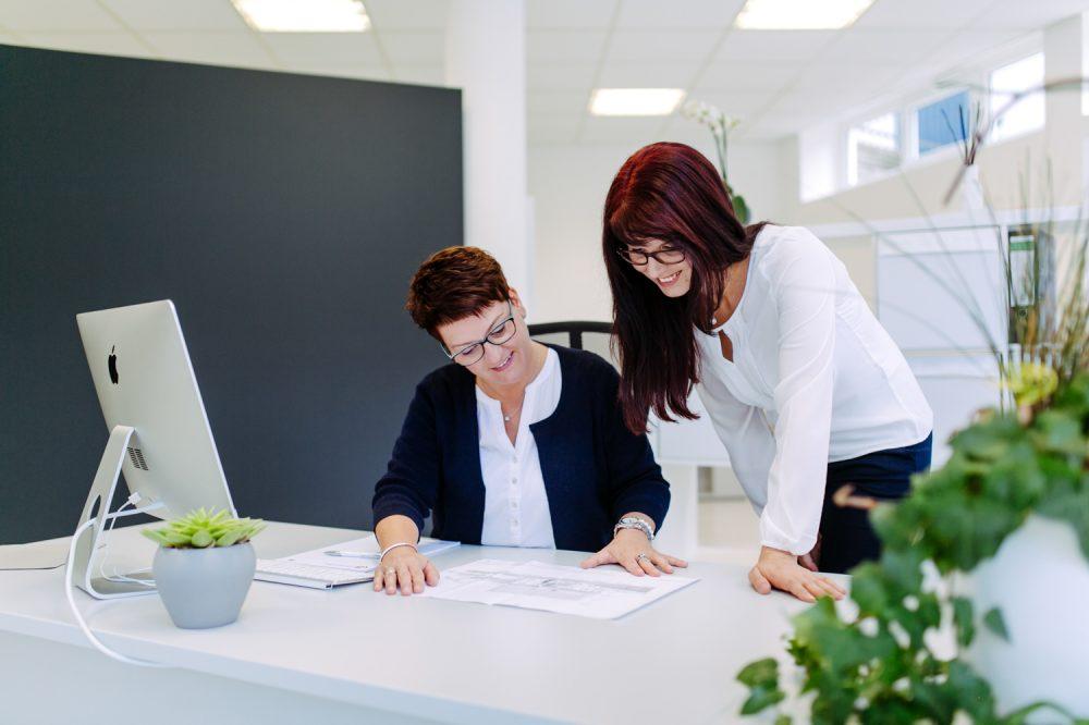 Zwei Mitarbeiterinnen fotografiert im Gespräch am Schreibtisch
